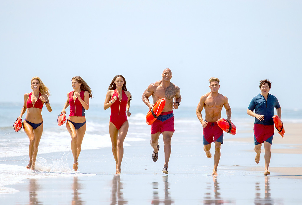 """. Kelly Rohrbach as CJ Parker, Alexandra Daddario as Summer, Ilfenesh Hadera as Stephanie Holden, Dwayne Johnson as Mitch Buchannon, Zac Efron as Matt Brody and Jon Bass as Ronnie in \""""Baywatch,\"""" in theaters May 26. (Paramount Pictures)"""