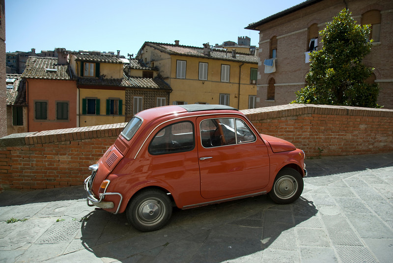 Vintage vehicle parked on a street in Siena, Italy