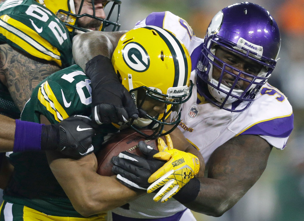 Description of . Minnesota Vikings defensive tackle Fred Evans (90) tackles Green Bay Packers wide receiver Randall Cobb (18) during the first half of an NFL wild card playoff football game Saturday, Jan. 5, 2013, in Green Bay, Wis. (AP Photo/Jeffrey Phelps)