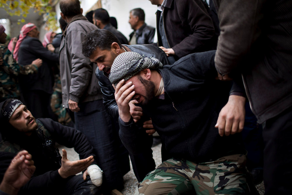 Description of . A Free Syrian Army fighter cries during the funeral of his comrade killed by the Syrian Army in Azaz, Syria, Thursday, Dec .13, 2012. (AP Photo/Manu Brabo)