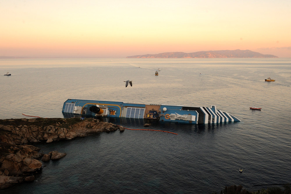 ". Cruise ship Costa Concordia lies stricken off the shore of the island of Giglio on January 18, 2012 in Giglio Porto, Italy. The official death toll is now 11, with a further 24 people still missing. The rescue operation was temporarily suspended earlier due to the ship moving as it slowly sinks further into the sea. ""Costa Concordia crash\"" ranked as Google\'s fifth most searched trending event of 2012. (Photo by Tullio M. Puglia/Getty Images)"