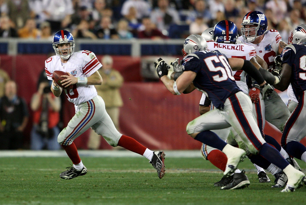 Description of . Eli Manning #10 of the New York Giants scrambles away from th New England Patriots defense to throw a 32 yard pass to David Tyree #85 of the Giants during the four quarter of Super Bowl XLII on February 3, 2008 at the University of Phoenix Stadium in Glendale, Arizona.  (Photo by Andy Lyons/Getty Images)