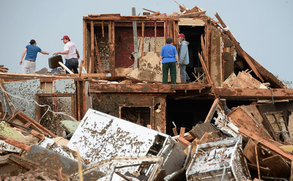 . People look for belongings after a tornado struck Moore, Oklahoma, May 20, 2013. A 2-mile-wide (3-km-wide) tornado tore through the Oklahoma City suburb of Moore on Monday, killing at least 51 people while destroying entire tracts of homes, piling cars atop one another, and trapping two dozen school children beneath rubble. REUTERS/Gene Blevins