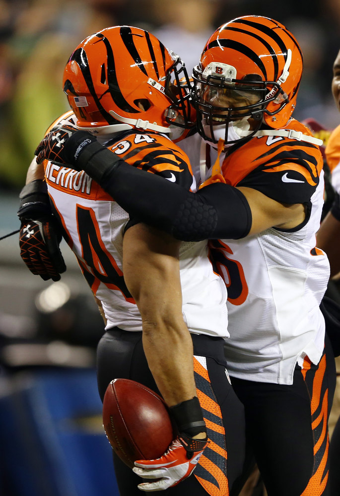 Description of . Dan Herron #34 of the Cincinnati Bengals is congratulated by teammates Taylor Mays #27 after Herron recovered a fumble from his blocked punt in the first quarter against the Philadelphia Eagles on December 13, 2012 at Lincoln Financial Field in Philadelphia, Pennsylvania.  (Photo by Elsa/Getty Images)