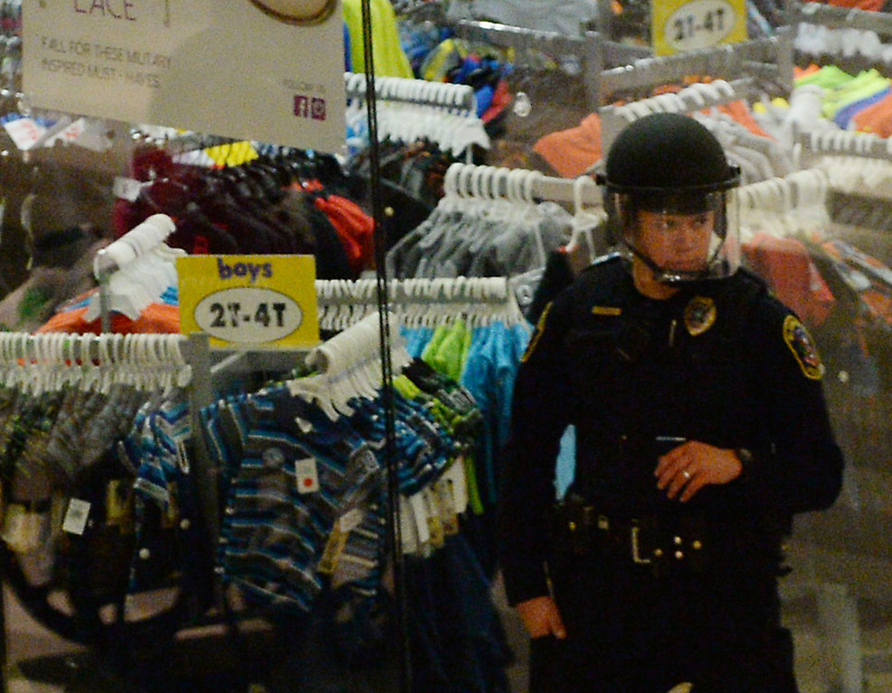 . A police officer watches the entrance of a store. (Pioneer Press: John Autey)