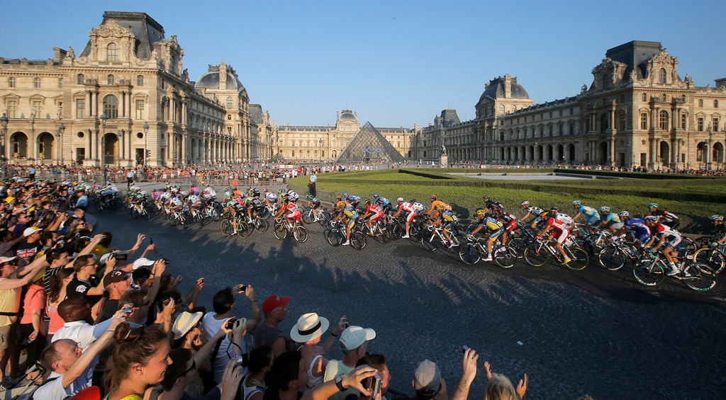. The pack rides through the courtyard of the Louvre museum, during the 21st and last stage of the 100th edition of the Tour de France cycling race over 133.5 kilometers (83.4 miles) with start in Versailles and finish in Paris, France, Sunday July 21 2013.  (AP Photo/Laurent Cipriani)