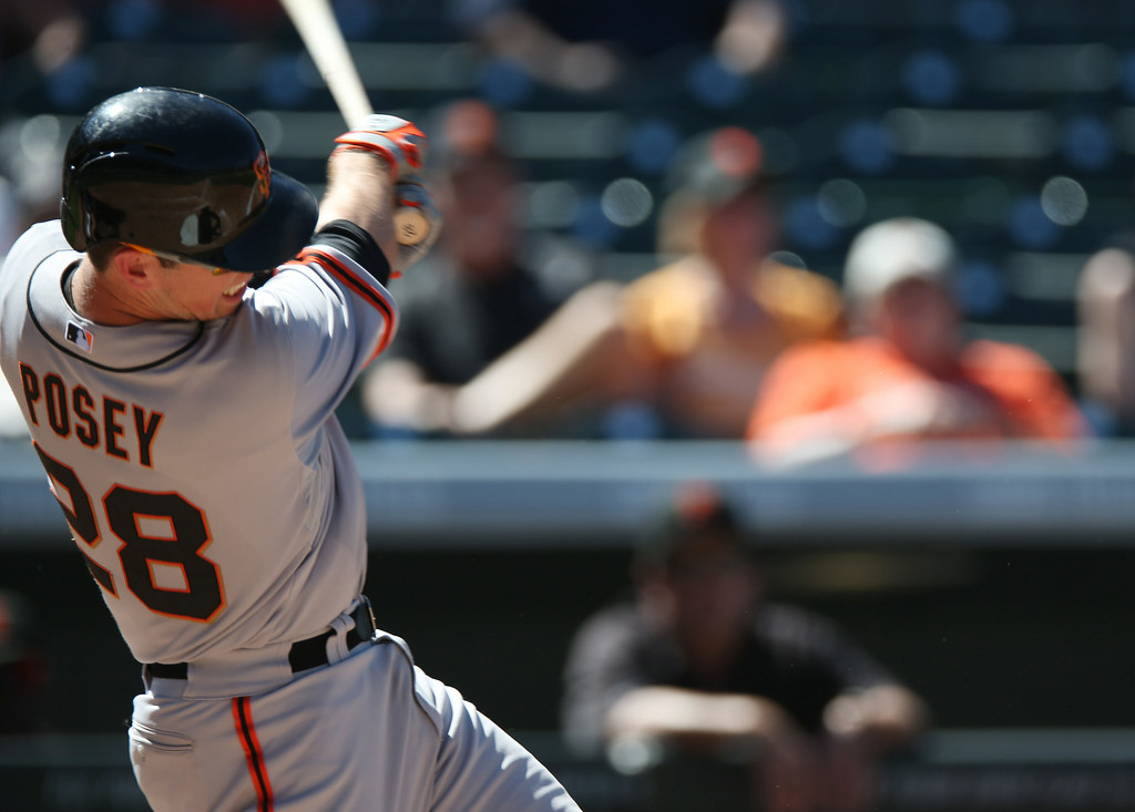 . San Francisco Giants\' Buster Posey follows through on an RBI single against the Colorado Rockies in the fifth inning of the Rockies\' 9-2 victory in a baseball game in Denver on Wednesday, Sept. 3, 2014. (AP Photo/David Zalubowski)