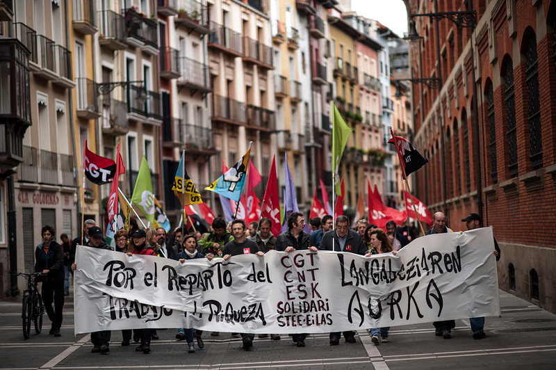 . Workers march on the street holding a banner which reads:  \'\'For the distribution the work and wealth\'\', during May Day, in Pamplona northern Spain, Thursday, May 1, 2014. Tens of thousands of workers marked May Day in European cities with a mix of anger and gloom over austerity measures imposed by leaders trying to contain the eurozone\'s intractable debt crisis.(AP Photo/Alvaro Barrientos)