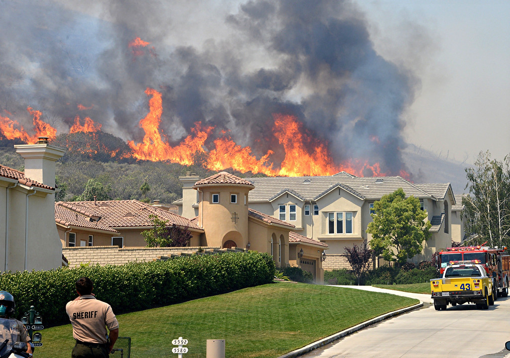 . Firefighters provide structure protection on Via Mira Flores in Thousand Oaks during the Springs fire as flames approach houses.