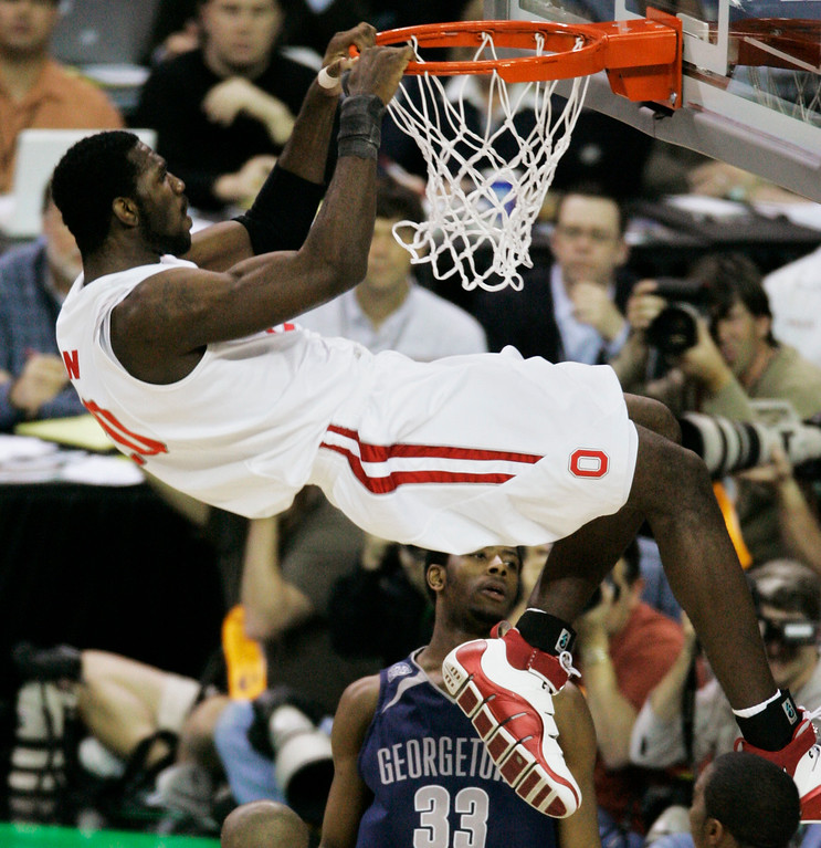 . Georgetown\'s Patrick Ewing Jr. (33) watches as Ohio State center Greg Oden hangs off the basket after dunking the ball during the second half of a Final Four semifinal basketball game at the Georgia Dome in Atlanta, Saturday, March 31, 2007. (AP Photo/Charlie Neibergall)