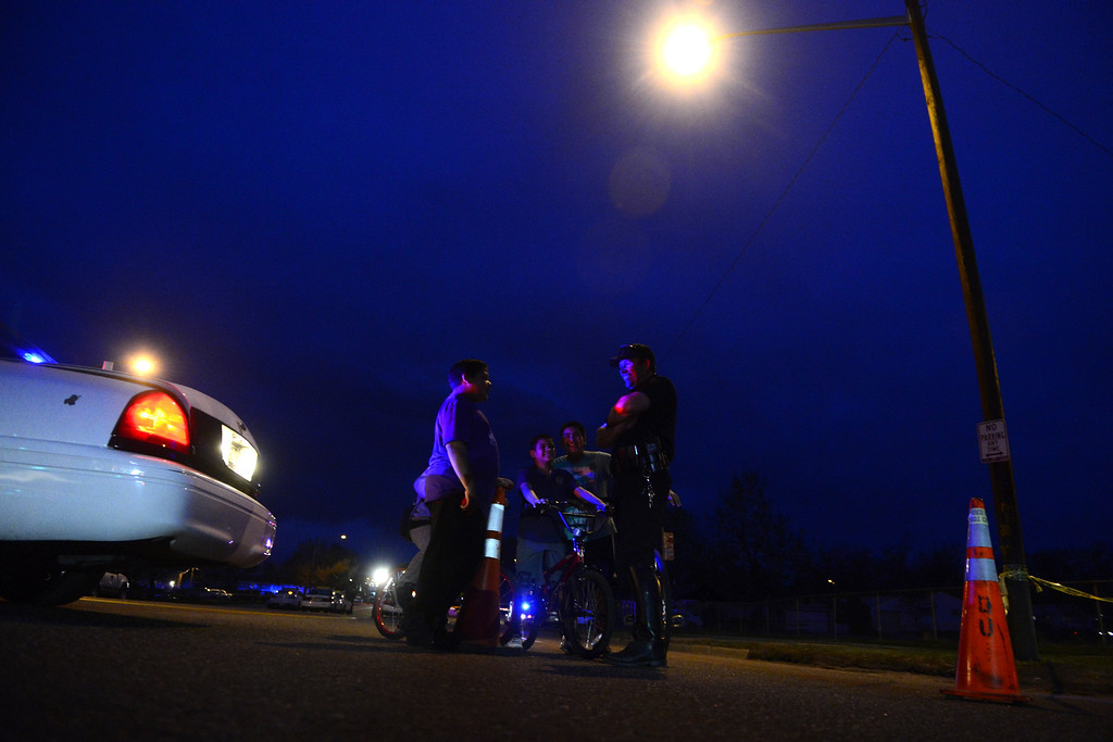 . DENVER, CO - MAY 14: Traffic officer Luke Palmatier entertains a group of neighborhood children as police investigate the scene of an officer-involved shooting near the intersection of Harvard and Federal Boulevard. (Photo by AAron Ontiveroz/The Denver Post)