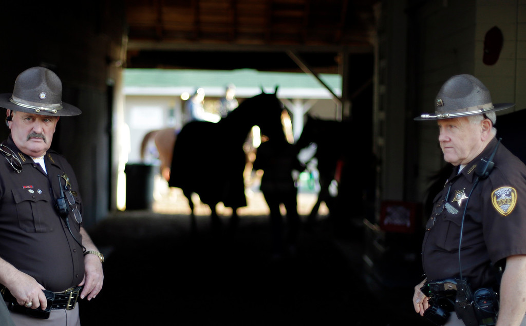 . Police stand guard outside the barn of Kentucky Derby hopeful Overanalyze at Churchill Downs Wednesday, May 1, 2013, in Louisville, Ky. (AP Photo/David Goldman)