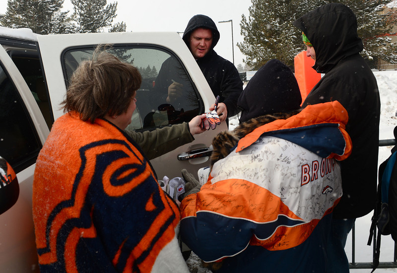 . Denver Broncos defensive tackle Mitch Unrein hands gloves, shoes and autographs to fans outside of Dove Valley as members of the team leave for the season in Englewood, Co on February 4, 2014. (Photo By Helen H. Richardson/ The Denver Post)
