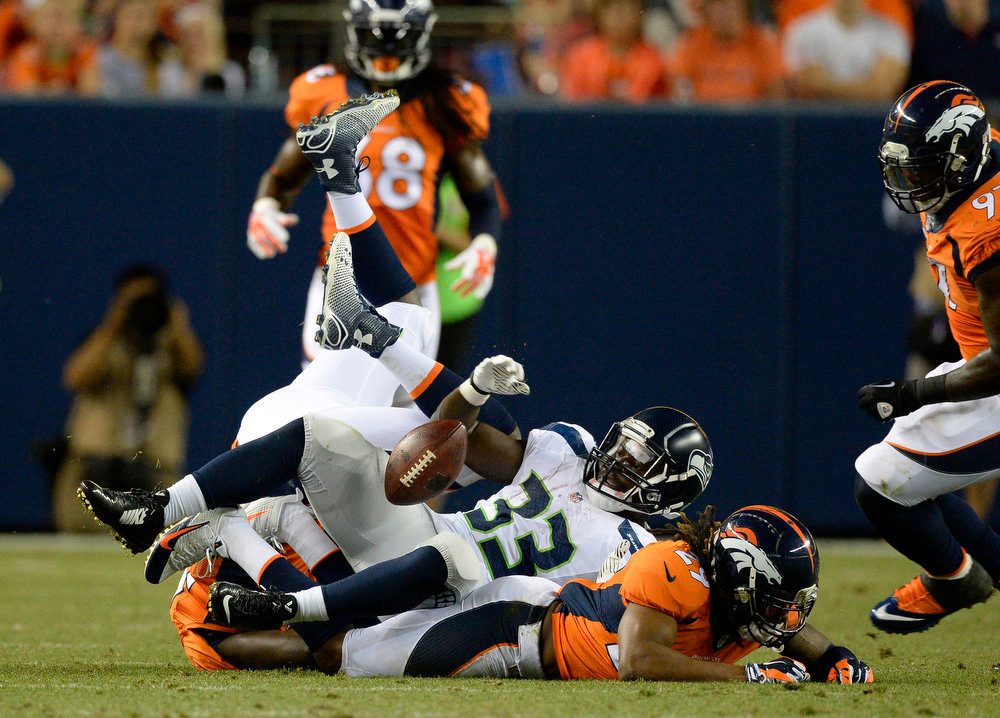 . Seattle Seahawks running back Christine Michael (33) fumbles the ball after getting hit by Denver Broncos cornerback Bradley Roby (29) during the second quarter August 7, 2014 at Sports Authority Field at Mile High Stadium.  (Photo by John Leyba/The Denver Post)