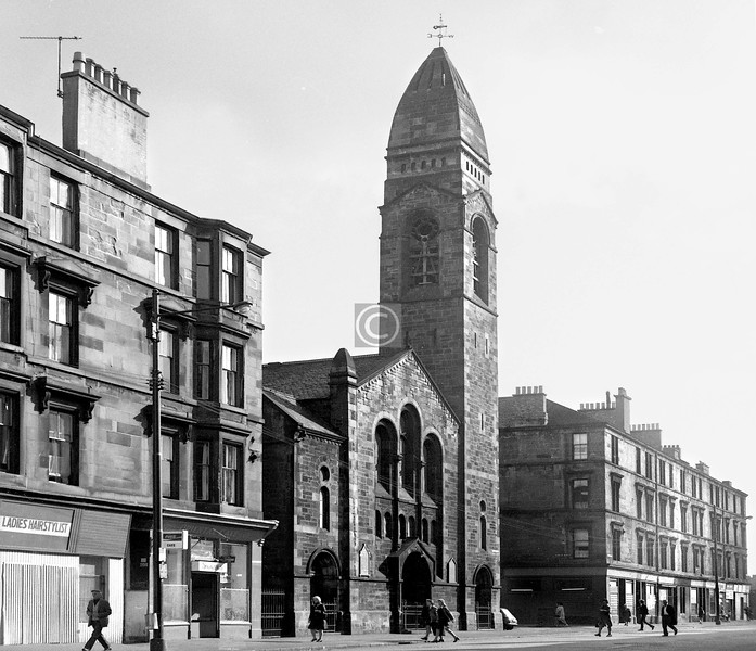 Crown St, east side at Kidston St.   St Ninian's Parish Church.    Crown St was still reasonably well populated (though not for much longer), as can be seen from the number of people making their homeward way at about 5pm on Thursday 30th August 1973