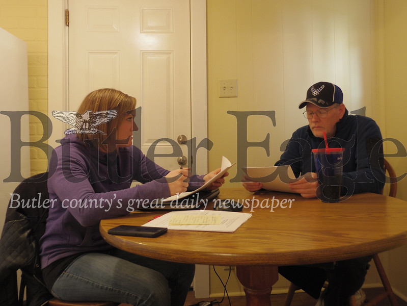 Roger Smith, an air force veteran, and April Petit, a service coordinator with Veterans Leadership Program of Western Pennsylvania, go over paperwork for Smith's new apartment.
