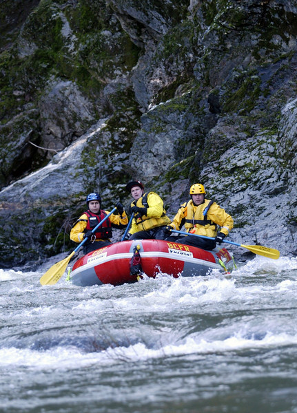 Butte Co./CDF Firefighter Miguel Watson, Capt. Chad Porter, and Firefighter Mike Conaty (left to right) navigate around a rock as they ride the rapids for a trip 6 miles, from Rich Bar to Belden Town down the North Fork of the Feather River in Plumas County for Butte Co./CDF Whitewater Boat Rescue training Tuesday. - halley photo 1/24/06