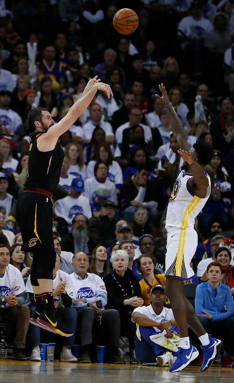 . Cleveland Cavaliers forward Kevin Love (0) shoots a 3-point shot over Golden State Warriors forward Jordan Bell (2) during the second half of an NBA basketball game in Oakland, Calif., Monday, Dec. 25, 2017. The Warriors won 99-92. (AP Photo/Tony Avelar)