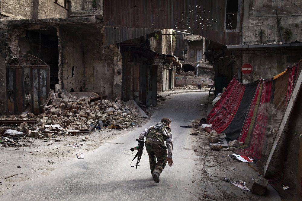 """. A Syrian rebel crosses a street while trying to dodge sniper fire in the old city of Aleppo in northern Syria on March 11, 2013. Syria warned on March 12 it is ready to fight \""""for years\"""" against rebels, as world powers worked on a new initiative to find regime officials suitable for peace talks with the opposition.   JM LOPEZ/AFP/Getty Images"""