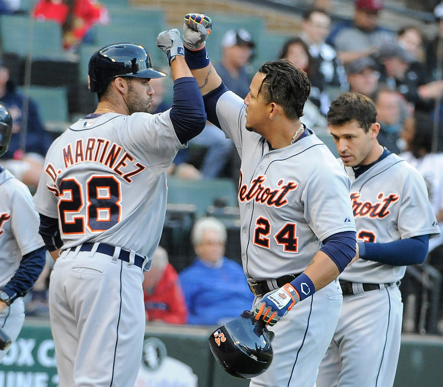 . Detroit Tigers\' Miguel Cabrera (24) is greeted by J.D. Martinez (28) after hitting a two-run homer against the Chicago White Sox during the fifth inning of a baseball game, Saturday, June 6, 2015 in Chicago.  (AP Photo/David Banks)