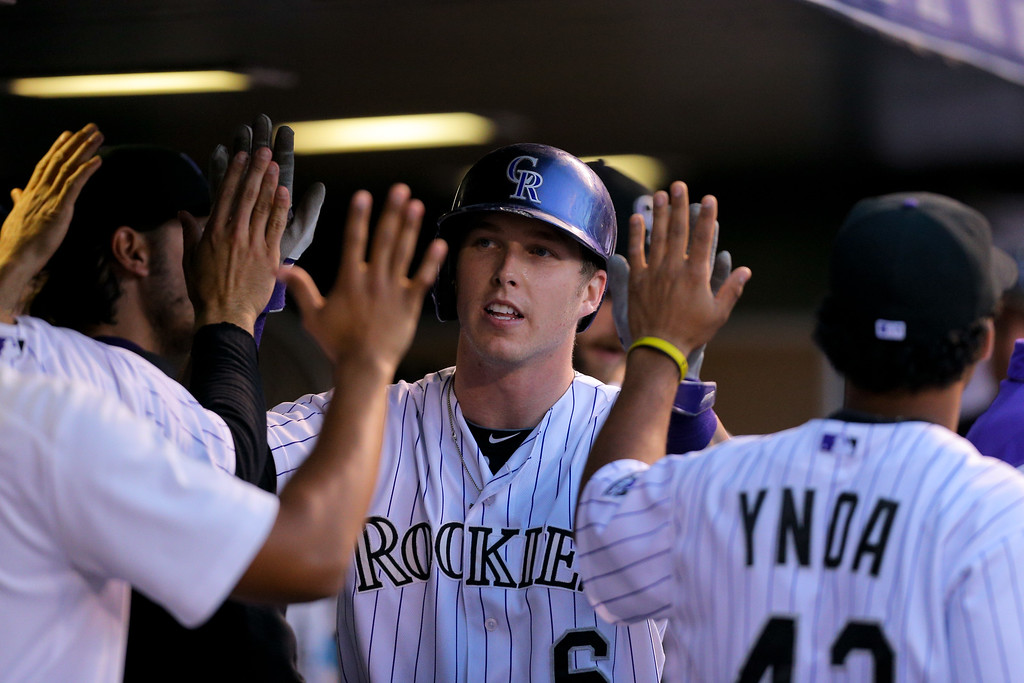 . DENVER, CO - SEPTEMBER 6:  Corey Dickerson #6 of the Colorado Rockies celebrates in the dugout after scoring during the third inning against the San Diego Padres at Coors Field on September 6, 2014 in Denver, Colorado. (Photo by Justin Edmonds/Getty Images)