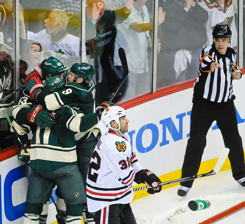 . Minnesota left wing Zach Parise, center, is hugged after scoring the game-tying goal by teammates Charlie Coyle, left, and Mikko Koivu in the third period against the Blackhawks. In the foreground is Chicago defenseman Michal Rozsival.  (Pioneer Press: Ben Garvin)