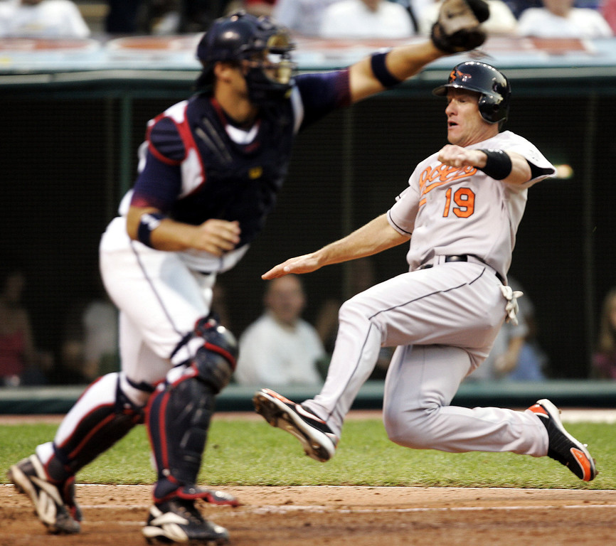 . JEFF CONINE -- Baltimore Orioles\' Jeff Conine (19) scores on Ramon Hernandez\'s two-run single as Cleveland Indians catcher Kelly Shoppach waits for the ball in the fourth inning of a baseball game on  July 8, 2006, in Cleveland. (AP Photo/Tony Dejak)