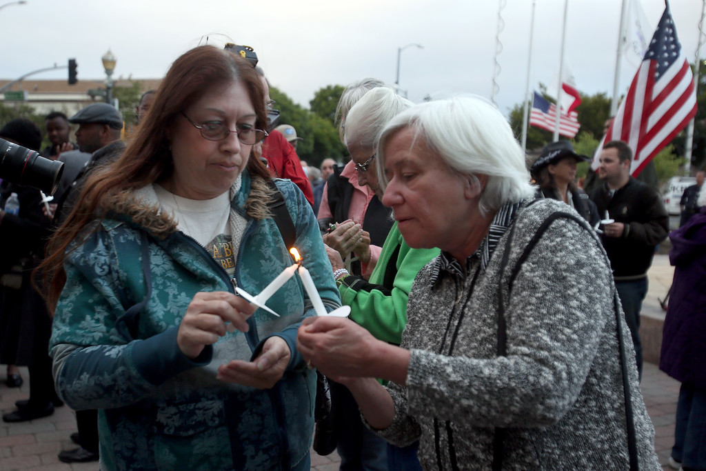 . Marisa Leasure, left, and Hayward Mayor Barbara Halliday light candles during a vigil for slain Hayward police Sgt. Scott Lunger at Hayward City Hall in Hayward, Calif., on Wednesday, July 22, 2015. Lunger was killed during a traffic stop early Wednesday. (Ray Chavez/Bay Area News Group)