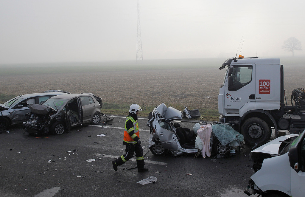 . A firefighter walks past the wreckage of some cars on the A19 highway in Zonnebeke, western Belgium, Tuesday, Dec.3, 2013.  (AP Photo/Yves Logghe)