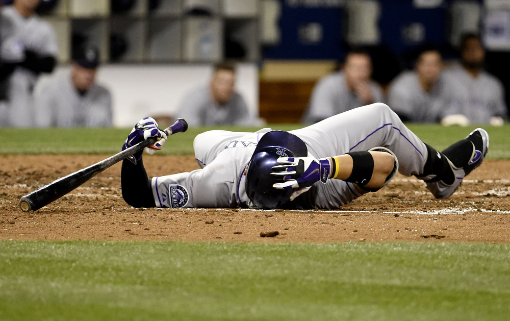 . SAN DIEGO, CA - APRIL 15:  Carlos Gonzalez of the Colorado Rockies falls to the ground after being brushed back by a pitch during the fifth inning of a baseball game against the San Diego Padres at Petco Park April 15, 2014 in San Diego, California.  All uniformed team members are wearing jersey number 42 in honor of Jackie Robinson Day.  (Photo by Denis Poroy/Getty Images)