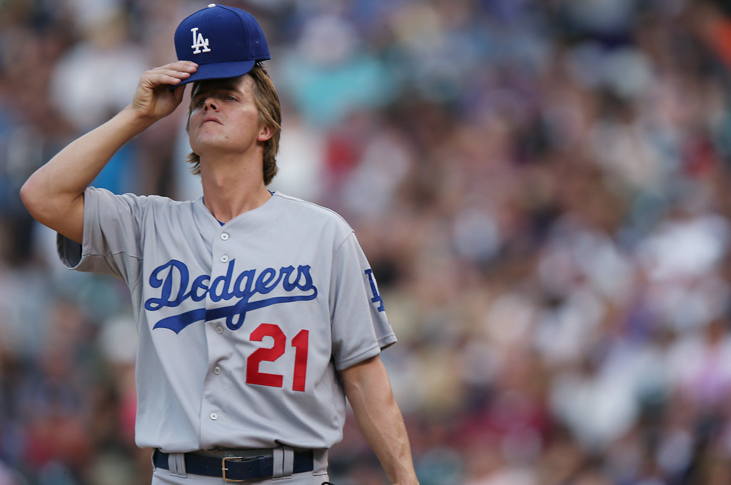 . Los Angeles Dodgers starting pitcher Zack Greinke adjusts his cap after giving up a single to Colorado Rockies\' Justin Morneau in the fourth inning of a baseball game in Denver on Thursday, July 3, 2014. (AP Photo/David Zalubowski)