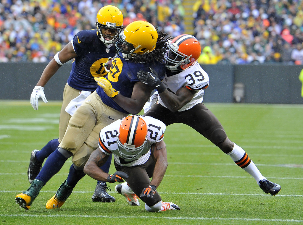 . Running back Eddie Lacy #27 of the Green Bay Packers (L) is brought down by defensive backs Chris Owens #21 and Julian Posey #38 of the Cleveland Browns after a 13-yard run during the first quarter at Lambeau Field on October 20, 2013 in Green Bay, Wisconsin.  (Photo by Brian Kersey/Getty Images)