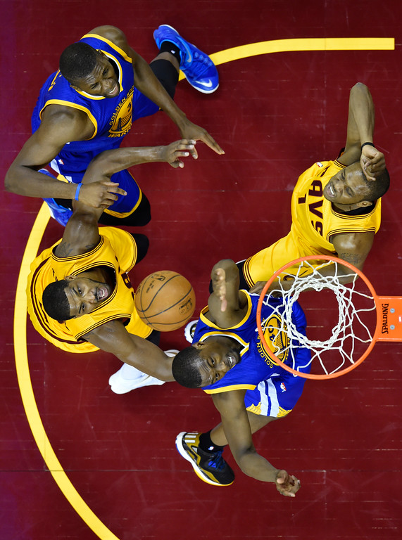 . Golden State Warriors forward Harrison Barnes, bottom, and teammate Festus Ezeli, top left, battle with Cleveland Cavaliers forward James Jones, top right, and Tristan Thompson for a rebound during the first half of Game 3 of basketball\'s NBA Finals in Cleveland, Tuesday, June 9, 2015. (Bob Donnan/Pool Photo via AP)