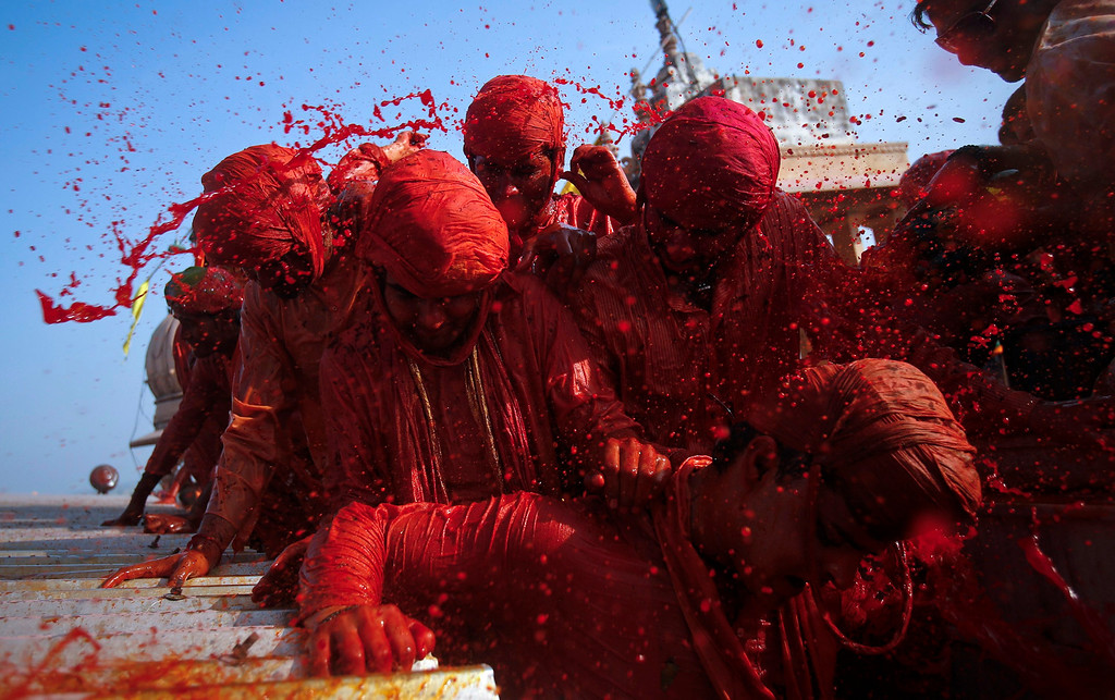 """. Hindu devotees throw coloured water at each other at a temple during \""""Lathmar Holi\"""" at the village of Barsana in the northern Indian state of Uttar Pradesh March 21, 2013. In a Holi tradition unique to Barsana and Nandgaon villages, men sing provocative songs to gain the attention of women, who then \""""beat\"""" them with bamboo sticks called \""""lathis\"""". Holi, also known as the Festival of Colours, heralds the beginning of spring and is celebrated all over India. REUTERS/Vivek Prakash"""