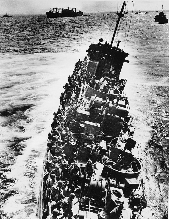 . A U.S. Coast Guard LCI, heavily listing to port, moves alongside a transport ship to evacuate her troops, during the initial Normandy landing operations in France, on June 6, 1944. Moments later the craft will capsize and sink. Note that helmeted infantrymen, with full packs, are all standing to starboard side of the ship. (AP Photo)