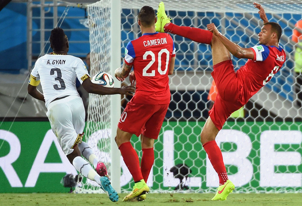 Description of . Ghana's forward Asamoah Gyan (L) vies with US defender Geoff Cameron (C) and US defender John Brooks during a Group G football match between Ghana and US at the Dunas Arena in Natal during the 2014 FIFA World Cup on June 16, 2014. AFP PHOTO / EMMANUEL DUNANDEMMANUEL DUNAND/AFP/Getty Images