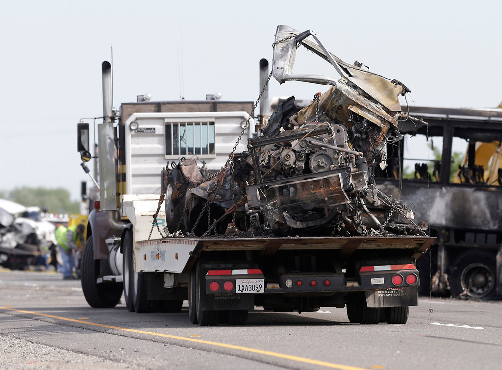 . The engine and front end of a FedEx truck involved in a fiery collision with a tour bus, sits on the back of a tow truck on Interstate 5, Friday, April 11, 2014 in Orland, Calif.  At least ten people were killed and dozens injured in the fiery crash,Thursday, between the truck and a bus carrying high school students on a visit to a Northern California College.(AP Photo/Rich Pedroncelli)