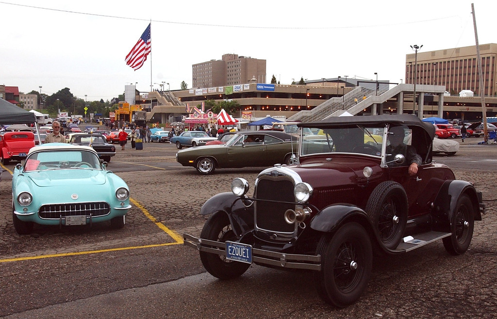 . A vintage car looks for a parking spot past a classic Corvette, left, on display in the parking lot of the Phoneix Plaza in downtown Pontiac during Friday night\'s Woodward Dream Cruise. The annual classic cruise goes from Pontiac to Ferndale covering 16-miles of classic cars, food & entertainment along the way.