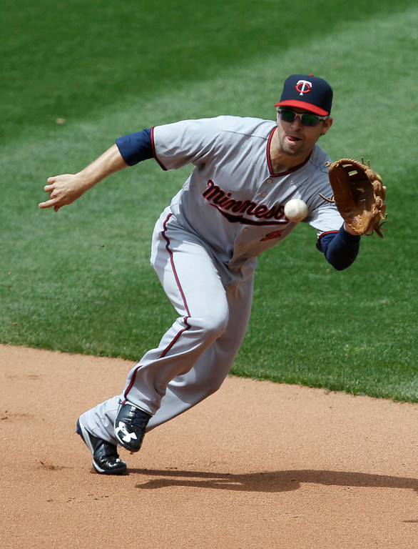 . Minnesota Twins\' Brian Dozier fields a ball hit by Cleveland Indians\' Michael Brantley in the fourth inning. Brantley was out at first base. (AP Photo/Tony Dejak)