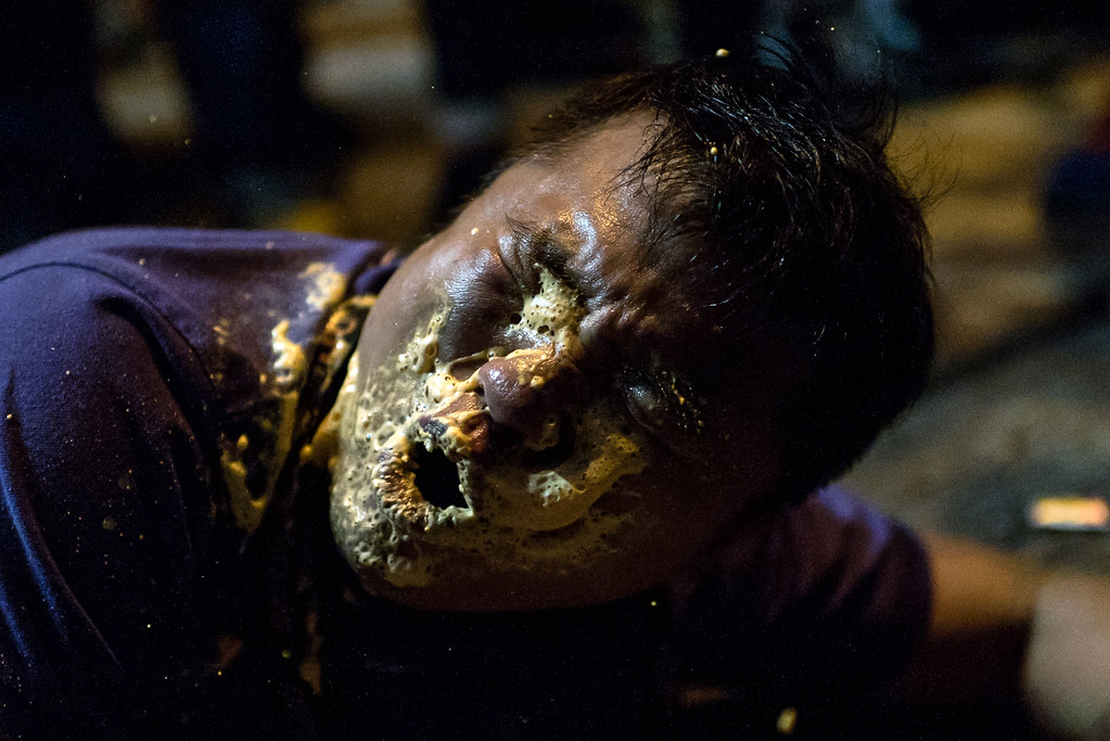 . A local Hong Kong journalist collapses in agony after being hit in the face with pepper spray by police in the Mongkok district of Hong Kong on October 17, 2014. Fresh clashes broke out in Hong Kong on October 17 as pro-democracy demonstrators attempted to take back a protest camp in a densely populated suburb that had been partially cleared by police earlier in the day. AFP PHOTO / ALEX  Ogle/AFP/Getty Images