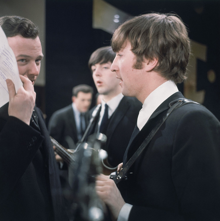". John Lennon of the Beatles is shown backstage speaking with manager Brian Epstein at the ""Ed Sullivan Show\"" in New York, Feb. 1964. In the background is basist Paul McCartney. (AP Photo)"