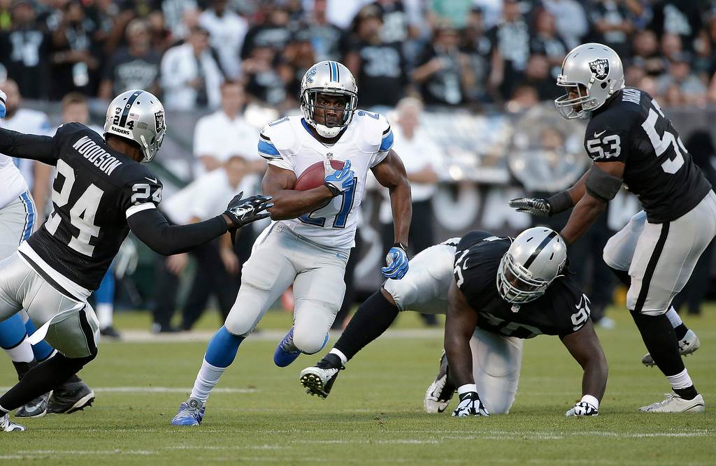 . Detroit Lions running back Reggie Bush (21) runs between Oakland Raiders cornerback Charles Woodson (24), defensive tackle Pat Sims (90), and linebacker Nick Roach (53) during the first quarter of an NFL preseason football game in Oakland, Calif., Friday, Aug. 15, 2014. (AP Photo/Marcio Jose Sanchez)