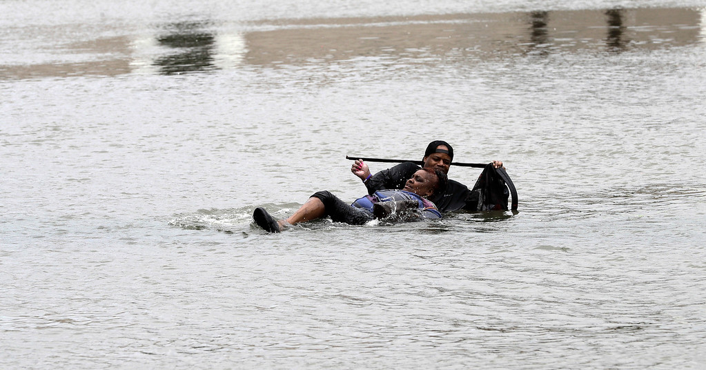 . A man helps a woman in floodwaters from Tropical Storm Harvey Sunday, Aug. 27, 2017, in Houston, Texas. The remnants of Hurricane Harvey sent devastating floods pouring into Houston Sunday as rising water chased thousands of people to rooftops or higher ground. (AP Photo/David J. Phillip)