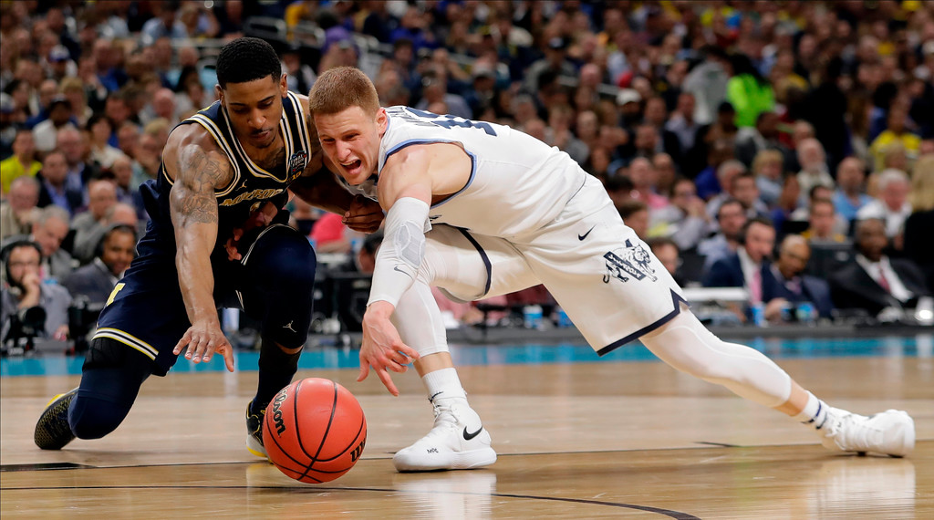 . Michigan\'s Charles Matthews, left and Villanova\'s Donte DiVincenzo chase the loose ball during the second half in the championship game of the Final Four NCAA college basketball tournament, Monday, April 2, 2018, in San Antonio. (AP Photo/Eric Gay)