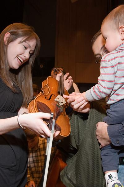 Rebecca Azhdam, violin, with child -- Hopkins Symphony Orchestra, March 2008