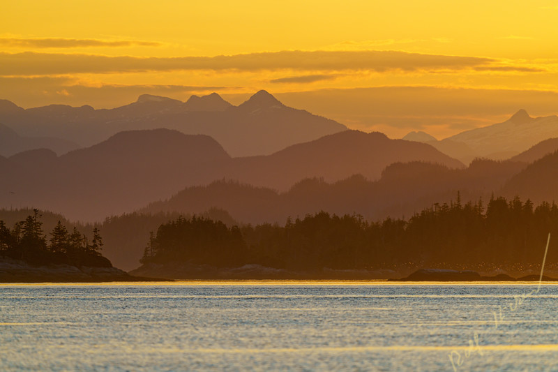 Looking over the Broughton Archipelago towards the British Columbia Coastal Mountains during a colorfull sunset in August, First Nations Territory, British Columbia, Canada.