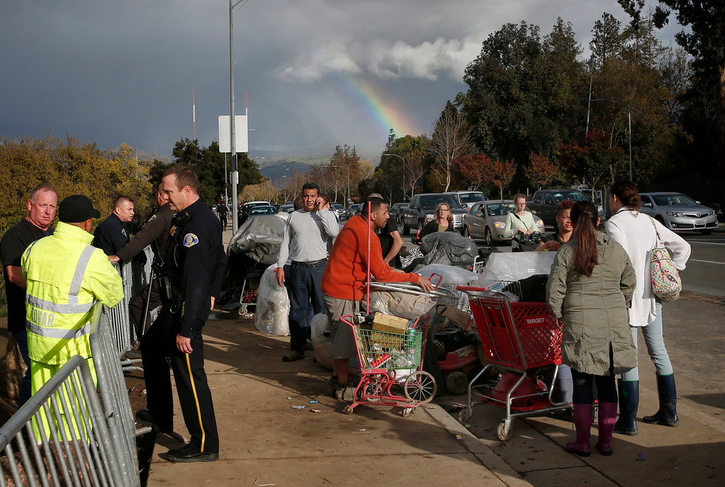 . A rainbow comes out in San Jose, Calif., as the Jungle homeless camp is closed filling Story Road with shopping carts, displaced people, clean-up crews and police officers Thursday afternoon, Dec. 4, 2014. (Karl Mondon/Bay Area News Group)
