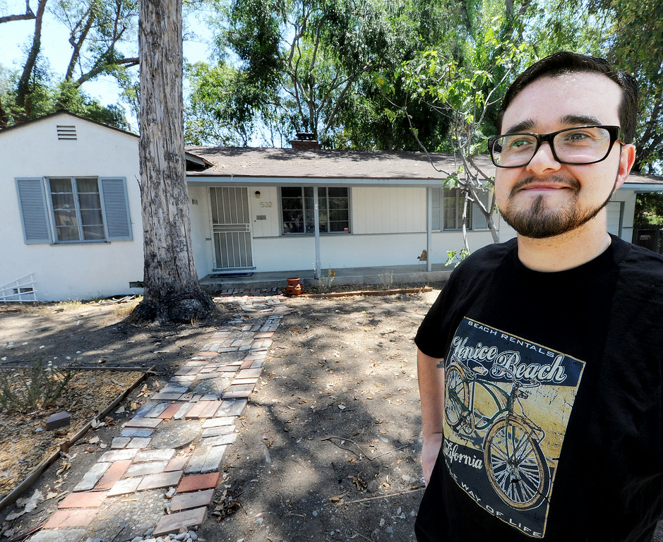 . Joel Alvarez standing in front of a Caltrans home that he has rented for three years at 532 Meridian Avenue in South Pasadena.  Alvarez who like the City of South Pasadena and its excellent schools is looking forward to having the opportunity to  purchase that home from Caltrans Tuesday, July 8, 2014. Fifty-three properties owned by Caltrans have gone back on the market after years of being state-owned rentals. The properties were once reserved to be demolished for the possible 710 freeway extension, but Caltrans now says they are outside the footprint of the five remaining options being studied by the agency to complete the freeway. Caltrans was also prompted to sell the homes by a state law passed last year.(Photo by Walt Mancini/Pasadena Star-News)