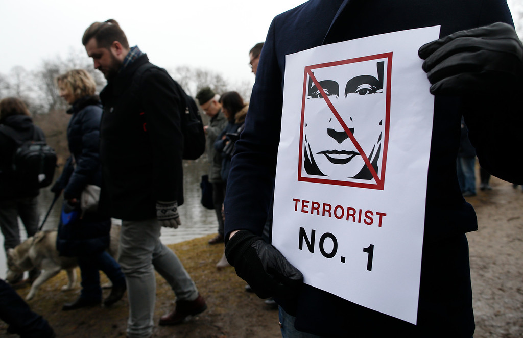 . A man holds a poster as people gather outside the Russian Embassy to pay their respect to Boris Nemtsov, the Russian opposition leader and sharp critic of Russian President Vladimir Putin, outside the Russian Embassy  in Vilnius, Lithuania, Sunday, March 1, 2015.  Nemtsov was gunned down Friday in Moscow near the Kremlin, just a day before a planned protest against the government. (AP Photo/Mindaugas Kulbis)