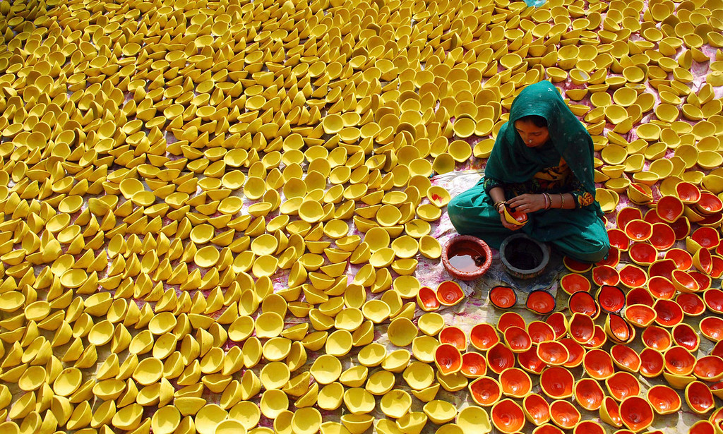. An Indian potter paints earthen lamps ahead of Diwali, or the Hindu festival of lights, in Amritsar, India on Wednesday, Oct. 30, 2013. The lamps, called diyas, are among the most popular Diwali decorations. (AP Photo/Prabhjot Gill, File)
